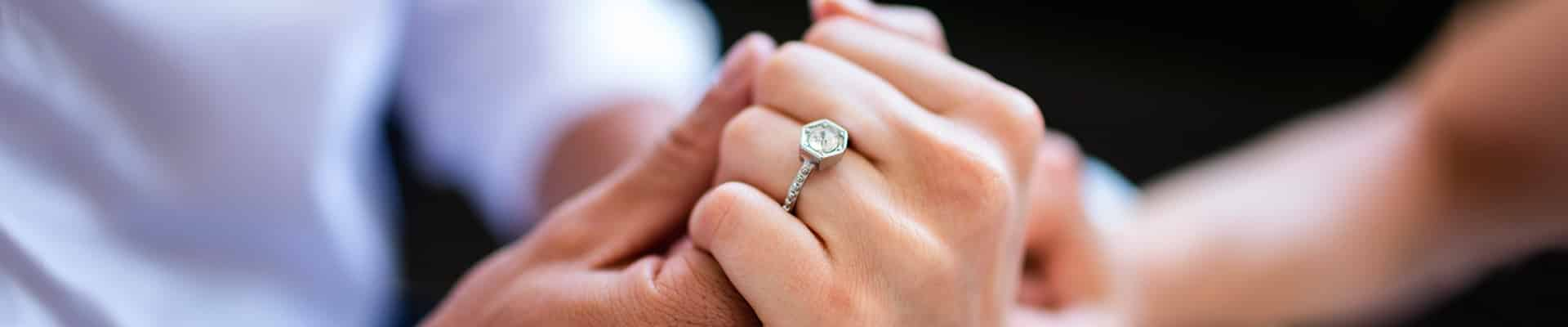 Couples hands embracing with ring